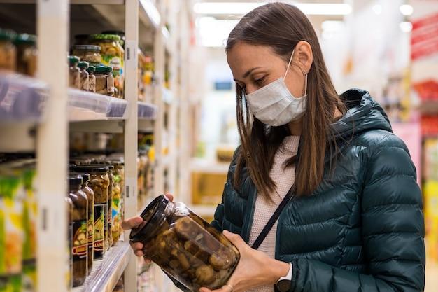 Jeune femme au masque médical sélectionne une nourriture en conserve au supermarché