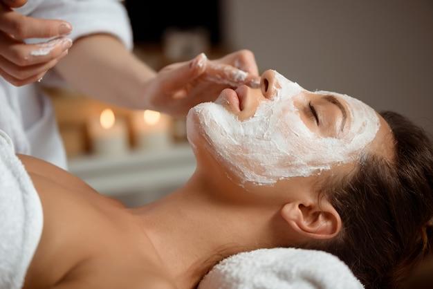 Jeune femme au masque pour le visage relaxant dans le salon spa.