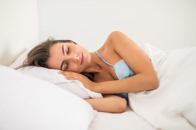 Jeune femme au repos au lit avec les mains à côté de sa tête sur l'oreiller.