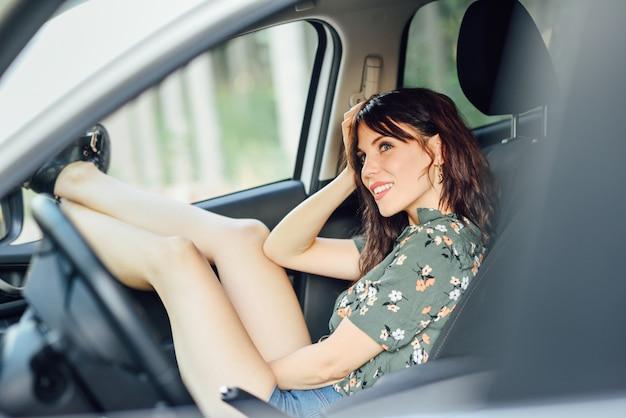 Jeune femme au repos dans une voiture blanche tirant ses pieds par la fenêtre.
