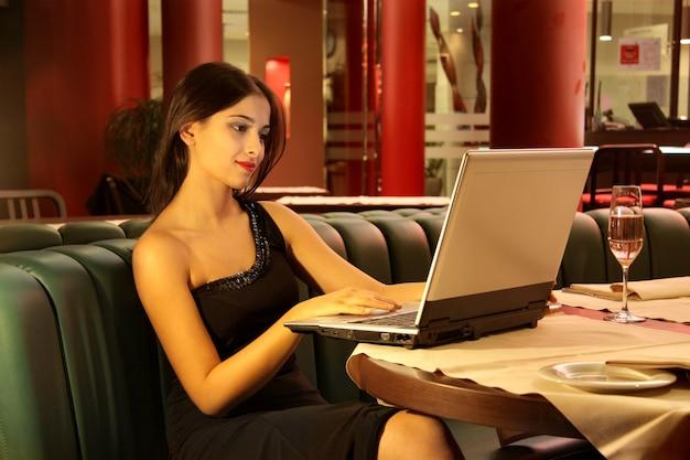 Jeune femme au restaurant avec ordinateur portable