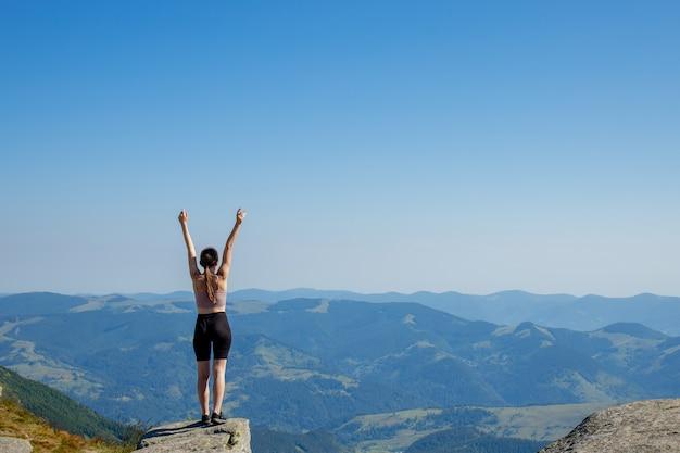 La jeune femme au sommet de la montagne leva les mains sur le ciel bleu