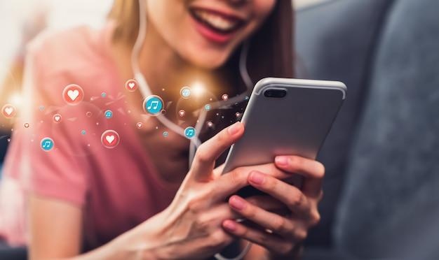 Une jeune femme au sourire heureux écoute de la musique avec des écouteurs et utilise des smartphones avec des icônes multimédias pendant les vacances à la maison.