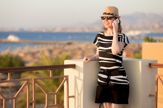 Jeune femme au téléphone dans la ville de la mer