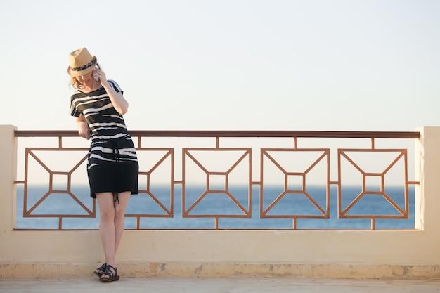 Jeune femme au téléphone sur la rue de la mer