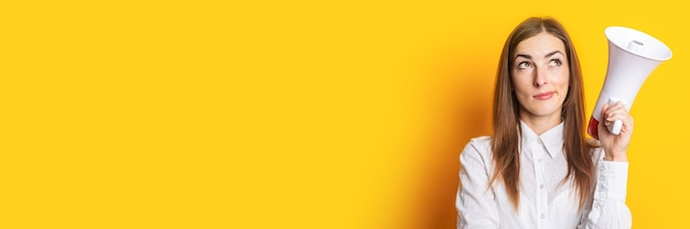 Jeune femme au visage pensif tient un mégaphone dans ses mains sur fond jaune. concept d'embauche, aide recherchée. bannière.