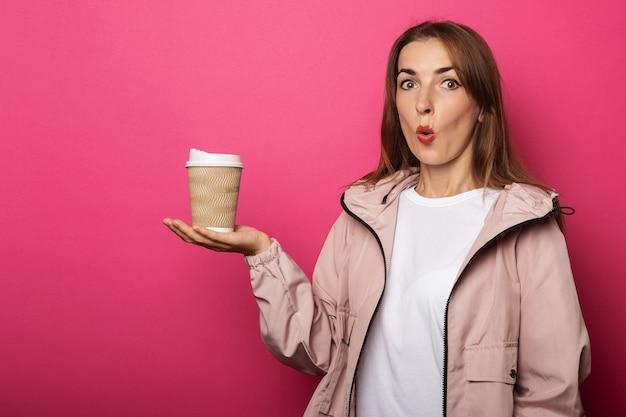 Jeune femme au visage surpris tenant une tasse de papier avec du café à la main sur une surface rose