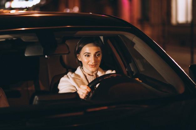 Jeune femme au volant de voiture la nuit