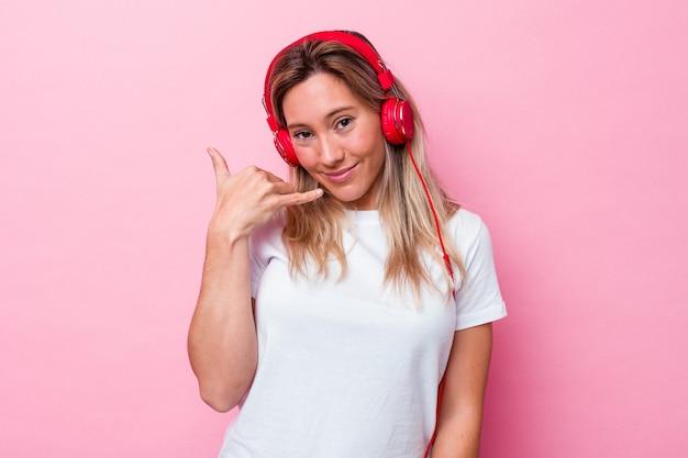 Jeune femme australienne écoutant de la musique isolée sur fond rose montrant un geste d'appel de téléphone portable avec les doigts.