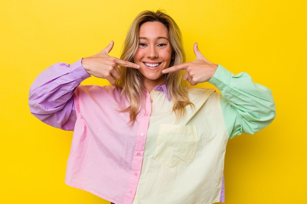 Jeune femme australienne isolée sourit, pointant du doigt la bouche.