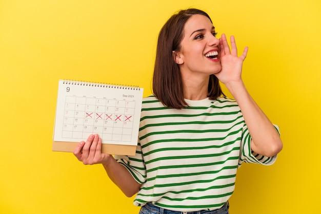 Jeune femme australienne tenant un calendrier isolé sur fond jaune criant et tenant la paume près de la bouche ouverte.
