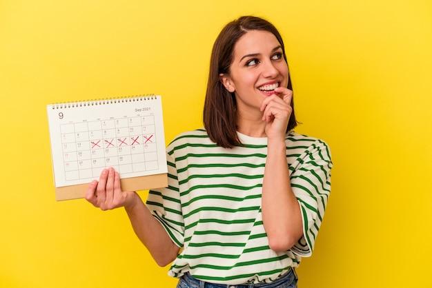 Jeune femme australienne tenant un calendrier isolé sur fond jaune détendue en pensant à quelque chose en regardant un espace de copie.