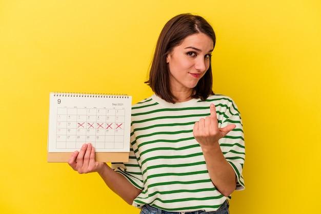 Jeune femme australienne tenant un calendrier isolé sur fond jaune pointant du doigt vers vous comme si vous vous invitiez à vous rapprocher.