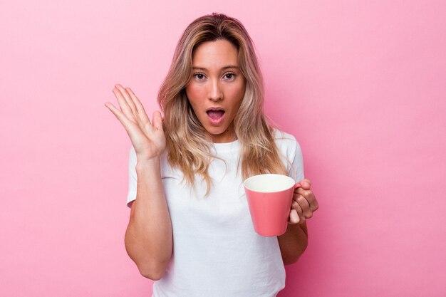 Jeune femme australienne tenant une tasse rose isolée sur fond rose surprise et choquée.