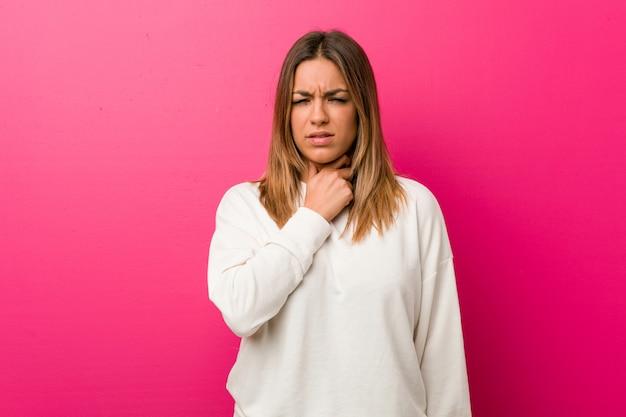 Jeune femme authentique, charismatique et réelle, une femme contre un mur a mal à la gorge à cause d'un virus ou d'une infection.