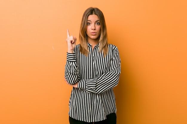 Jeune femme authentique de vraies personnes charismatiques contre un mur ayant une très bonne idée, concept de créativité.