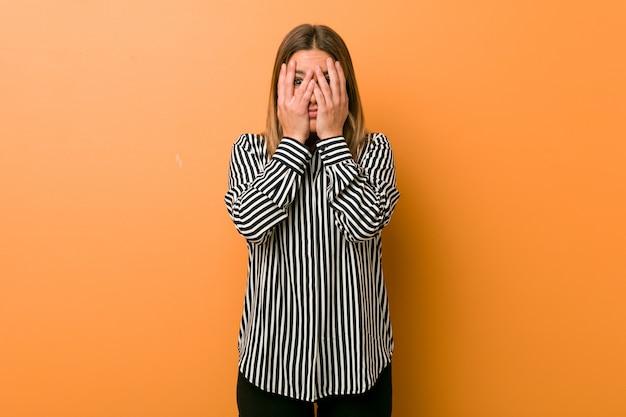 Jeune femme authentique, de vraies personnes charismatiques contre un mur, cligne des yeux, effrayée et nerveuse.