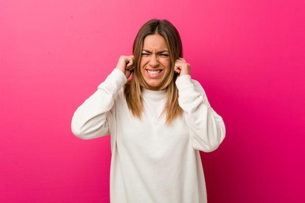 Jeune femme authentique de vraies personnes charismatiques contre un mur couvrant les oreilles avec les mains.