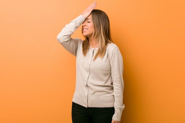 Jeune femme authentique, de vraies personnes charismatiques contre un mur, oubliant quelque chose, se gifle le front avec la paume de la main et ferme les yeux.