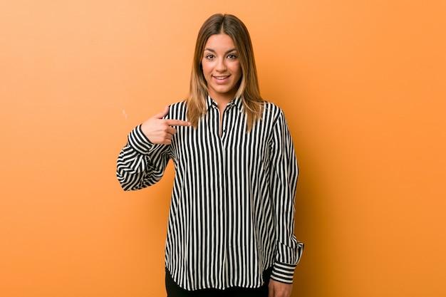 Jeune femme authentique de vraies personnes charismatiques contre un mur, pointant à la main une chemise, un espace copie, fière et confiante