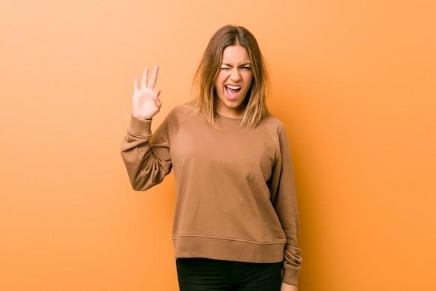 Jeune femme authentique de vrais gens charismatiques contre un mur fait un clin d'œil et tient un geste correct avec la main.