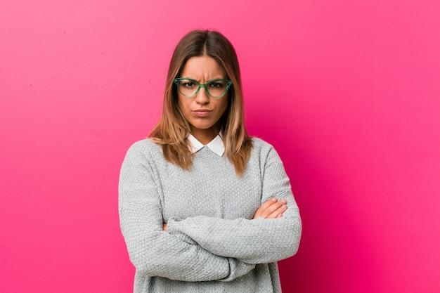 Jeune femme authentique de vrais gens charismatiques contre un mur fronçant les sourcils de mécontentement, les bras croisés.