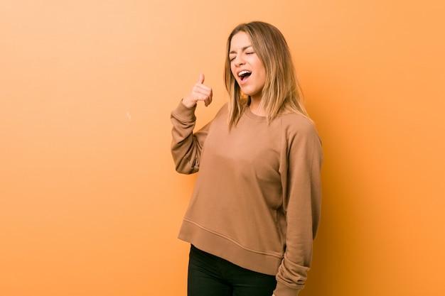 Jeune femme authentique de vrais gens charismatiques contre un mur montrant un geste d'appel de téléphone mobile avec les doigts.