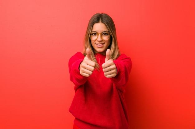 Jeune femme authentique de vrais gens charismatiques contre un mur avec le pouce levé, applaudit à quelque chose, soutient et respecte le concept.