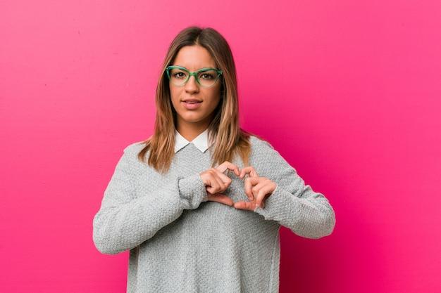Jeune femme authentique de vrais gens charismatiques contre un mur souriant et montrant une forme de coeur avec les mains.