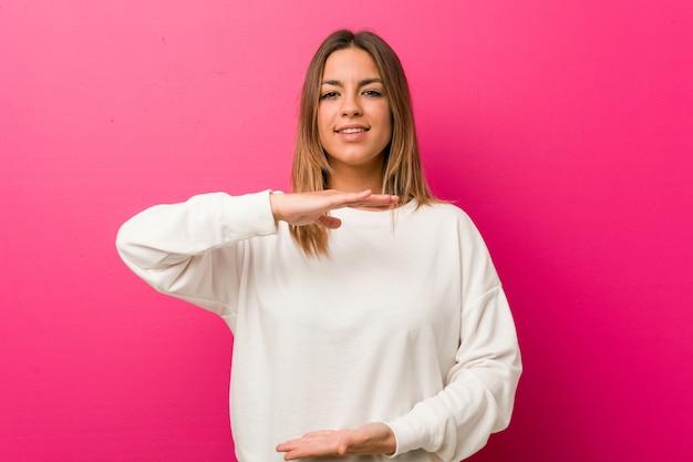 Jeune femme authentique de vrais gens charismatiques contre un mur tenant quelque chose avec les deux mains, présentation du produit.