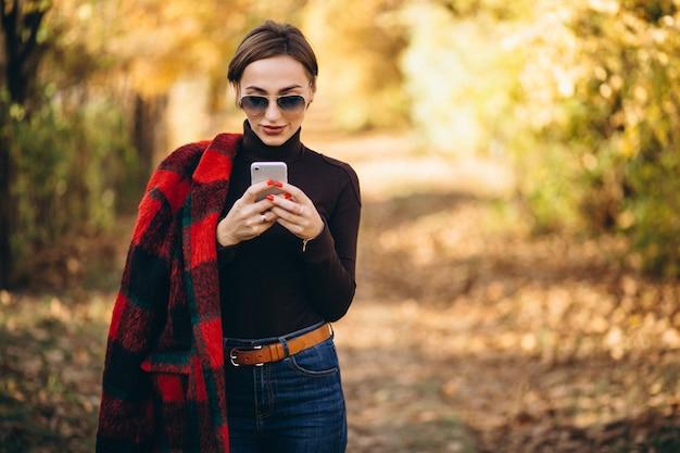 Jeune femme en automne parc à l'aide de téléphone