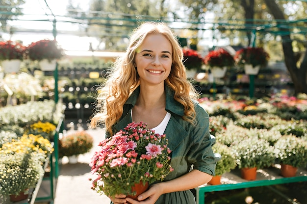 Jeune femme aux beaux cheveux blonds et sourire doux, vêtue d'une robe verte avec ceinture travaille en serre