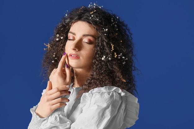 Jeune femme aux beaux cheveux bouclés sur bleu
