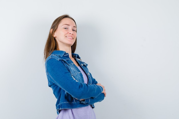 Jeune femme aux bras croisés en veste en jean et à la fierté. vue de face.