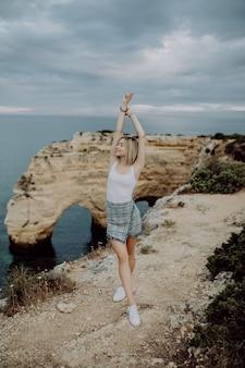 Jeune femme aux bras grands ouverts debout sur un rocher en face de la plage de l'océan au portugal