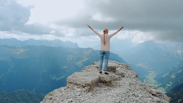 Jeune femme aux bras tendus profitant de la beauté de la nature sur le rocher de la montagne