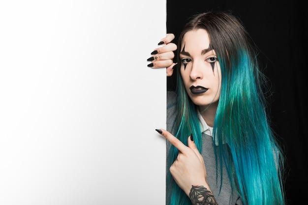 Jeune femme aux cheveux bleue pointant avec le doigt à bord