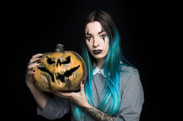 Jeune femme aux cheveux bleue posant avec citrouille