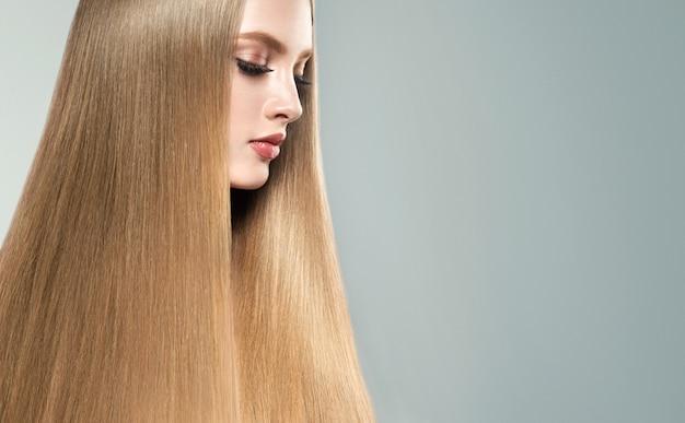 Jeune femme aux cheveux blonds aux cheveux raides et brillants.