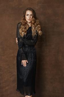 Une jeune femme aux cheveux blonds bouclés et au maquillage parfait portant une longue robe de soirée posant sur fond marron