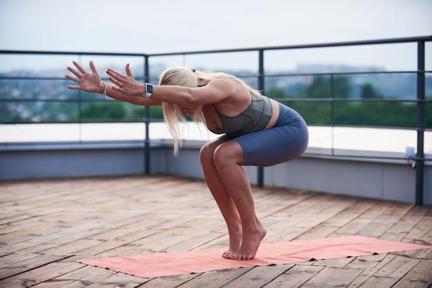 Jeune femme aux cheveux blonds et corps mince faire des exercices de yoga sur le tapis de yoga sur la terrasse en bois au coucher du soleil.