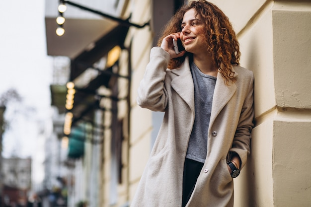 Jeune femme aux cheveux bouclés à l'aide de téléphone à la rue