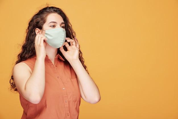Jeune femme aux cheveux bouclés en chemise sans manches ajustant le masque facial sur orange, prévention des coronavirus