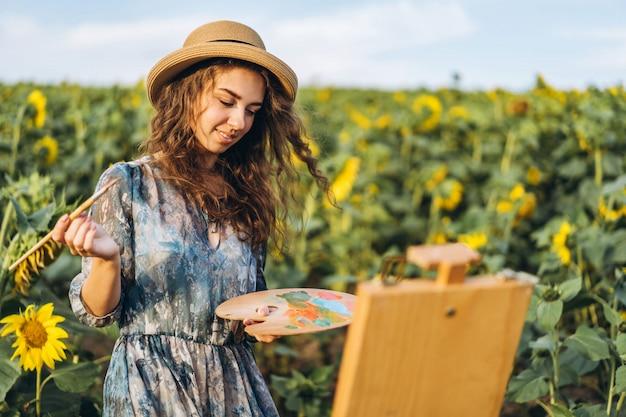 Une jeune femme aux cheveux bouclés et coiffée d'un chapeau peint dans la nature. une femme se tient dans un champ de tournesol par une belle journée