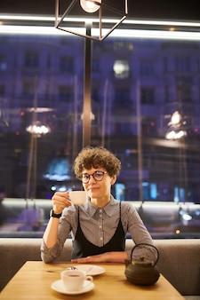 Jeune femme aux cheveux bouclés courts assis par table au café, se détendre et prendre du thé ou du café