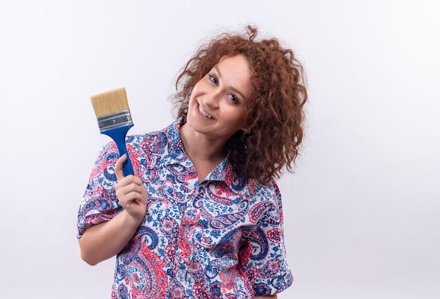 Jeune femme aux cheveux bouclés courts en chemise colorée tenant un pinceau souriant joyeusement debout sur un mur blanc