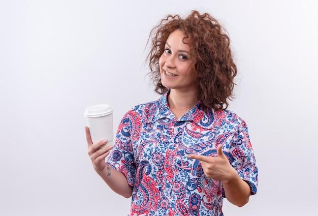Jeune femme aux cheveux bouclés courts en chemise colorée tenant une tasse de café pointant avec le doigt vers lui souriant debout sur un mur blanc