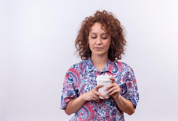 Jeune femme aux cheveux bouclés courts en chemise colorée tenant une tasse de café en le regardant avec une expression triste debout sur un mur blanc
