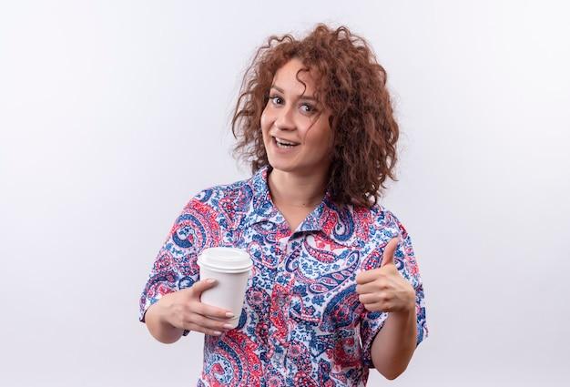 Jeune femme aux cheveux bouclés courts en chemise colorée tenant une tasse de café souriant montrant les pouces vers le haut debout sur un mur blanc