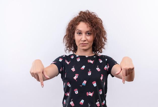 Jeune femme aux cheveux bouclés courts pointant les doigts vers le bas avec une expression sceptique debout sur un mur blanc